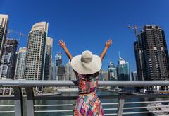 Girl in a wide-brimmed hat standing on the bridge and looks at the dubai mari Stock Photos