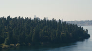 Stock Video Footage of Wide aerial shot of the trees in Seward Park on Bailey Peninsula eclipsing the