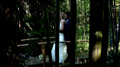 Bride and groom standing bridge pond wedding fashion white dress love forest pov Stock Footage
