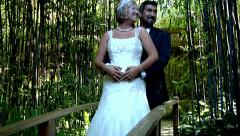 Bride and groom standing bridge pond wedding fashion white dress love forest Stock Footage