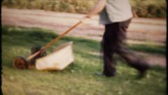 695 - cutting grass with new design mower - vintage film home movie  Stock Footage