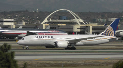 A Boeing Dreamliner waits as aircraft taxi, take off and land at LAX airport Stock Footage