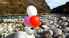 Three helium balloons are flown on the rocks by the river Stock Footage
