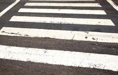 White painted lines on roadway denoting pedestrian crossing Stock Photos