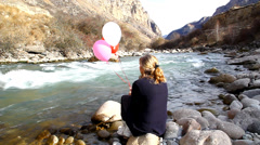 Woman with red gel balloon sits on a rock by the river Stock Footage