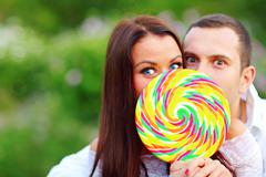 Young surprised couple covering their faces with huge colorful candy Stock Photos