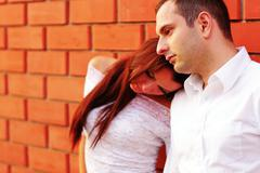 Sad pensive couple against brick wall Stock Photos