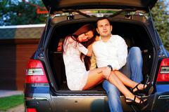 Romantic couple sitting in a trunk of modern car Stock Photos
