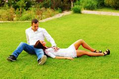 Young couple resting an the lawn in park Stock Photos
