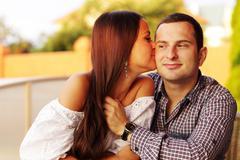 beautiful girl kissing her boyfriend on the cheek - stock photo