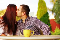 young romantic couple kissing in cafe outdoors - stock photo