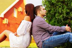 Young couple resting an the lawn in front of their house Stock Photos
