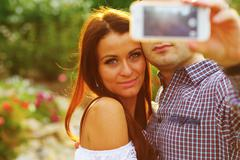 couple taking self-portrait photos with mobile smart phone - stock photo