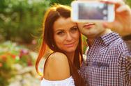 Stock Photo of couple taking self-portrait photos with mobile smart phone