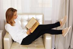 young woman reading a book in the armchair - stock photo
