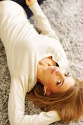 Young beautiful woman lying on the carpet at home Stock Photos