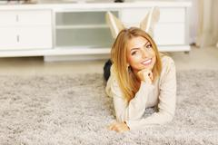 young beautiful woman lying on the carpet at home - stock photo