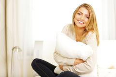 Young beautiful woman hugging pillow Stock Photos