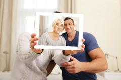 Stock Photo of happy couple taking a photo on the tablet pc