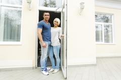Happy couple welcomes you in their new house Stock Photos