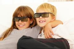 Brother and sister watching 3d movie at home Stock Photos