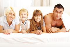 Happy young family lying on the bed and looking at camera Stock Photos