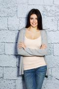 young beautiful happy woman in casual cloths against brick wall - stock photo