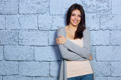 Young beautiful happy woman in casual cloths against brick wall Stock Photos