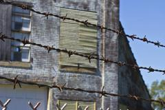 barbed wire guarding an abandoned factory - stock photo