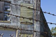 Stock Photo of barbed wire guarding an abandoned factory