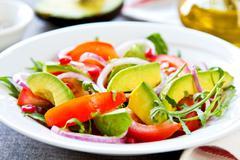 Avocado with Pomegranate and Rocket salad Stock Photos