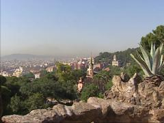 View from Park Guell at city of Barcelona + pan Tower of Gaudi House Stock Footage