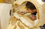 Stock Photo of woodworker building guitar in workshop