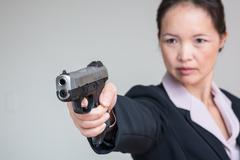 Woman aiming a hand gun Stock Photos