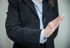 Woman signals denial with one hand Stock Photos