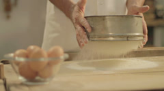 Baker hand throwing flour on the table - cinestyle Stock Footage