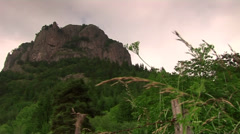 Rock on top a hill composition-road and green hill on top Stock Footage