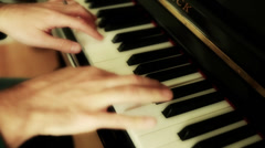 Stock Video Footage of a man playing a song on an upright piano