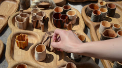 hand takes wooden hand carved stemware sold in market - stock footage