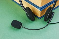 Stock Photo of headphones with a microphone and a stack of books on a green background