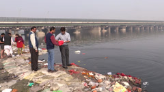 Girl and boy are performing a Hindu ritual at the bank of Yamuna River Stock Footage