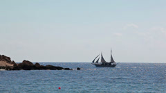 Two-masted sail ship sailing on the Mediterranean sea over rocky island, Cyprus Stock Footage