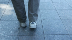 An old man slowly moves his feet while walking Stock Footage
