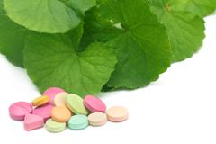 Medicinal thankuni leaves with pills Stock Photos