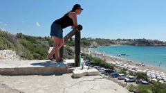 Young woman standing on viewpoint in Coral Bay and looking at seacost, Cyprus Stock Footage