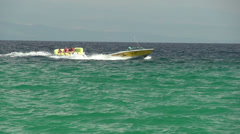 Speed boat pulling people on the rubber floater slow motion Stock Footage