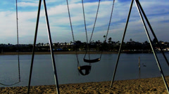 Empty Swings Swaying With Lake Behind - stock footage