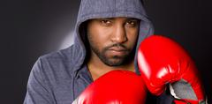Solo male athlete boxer strikes fighter pose hoodie red boxing gloves Stock Photos