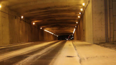 Driving through well-lit underpass at night Stock Footage