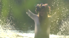 Stock Video Footage girl in wreaths of flowers splashing in the river - stock footage
